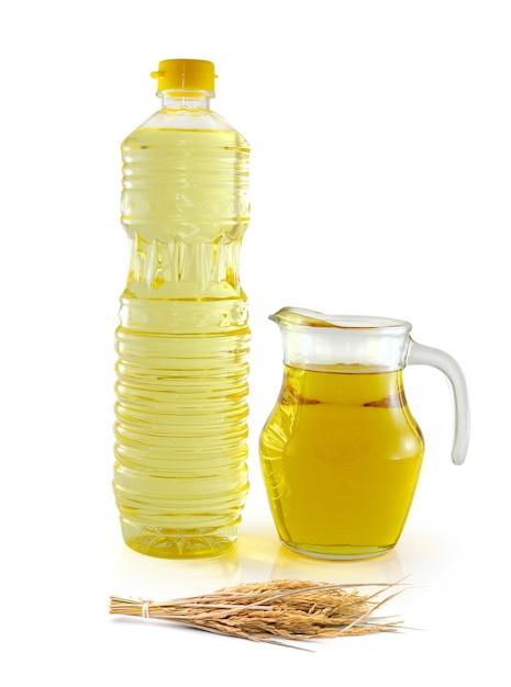 Масло из рисовых отрубей в бутылочном стакане с семенами и отрубями на белом Premium Фотографии
