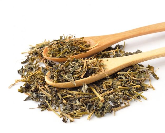 Ароматный зеленый сухой чай в ложке на белом Premium Фотографии