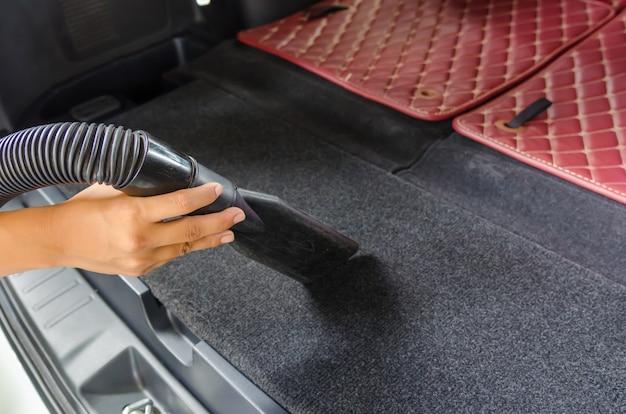車の掃除機をかける女性。 Premium写真