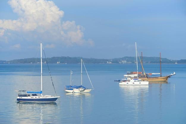 トロピカル近くの反射を伴う海の水上でのセイルボートとヨットの牧歌的な景色 Premium写真