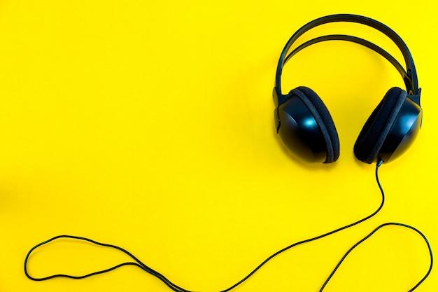 黄色の孤立した背景に対して黒のヘッドフォンのトップビュー Premium写真