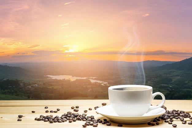 白いカップのコーヒーと自然の夕日を背景に木製のテーブルの上のコーヒー豆 Premium写真