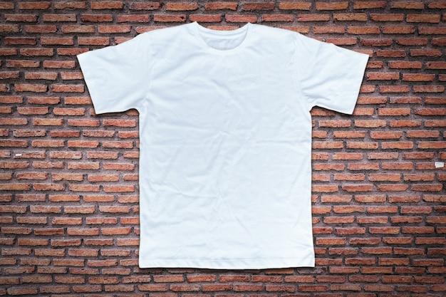 Белая футболка на фоне кирпичной стены. Premium Фотографии