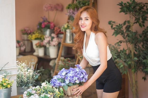 Улыбающаяся женщина флорист расставляет красивые цветы в цветочном магазине Premium Фотографии
