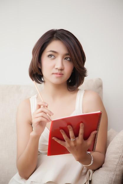 本と鉛筆を保持している若い美しいアジア女性 Premium写真