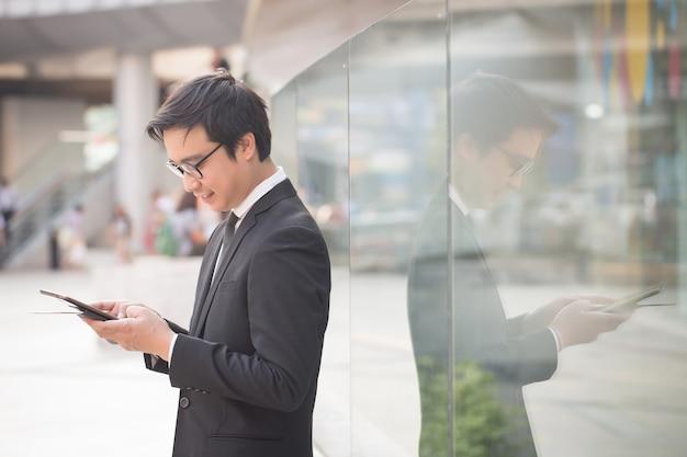 ビジネスの男性の笑みを浮かべての肖像画は、コンピューターのタブレットを使用して自信を持って見える Premium写真