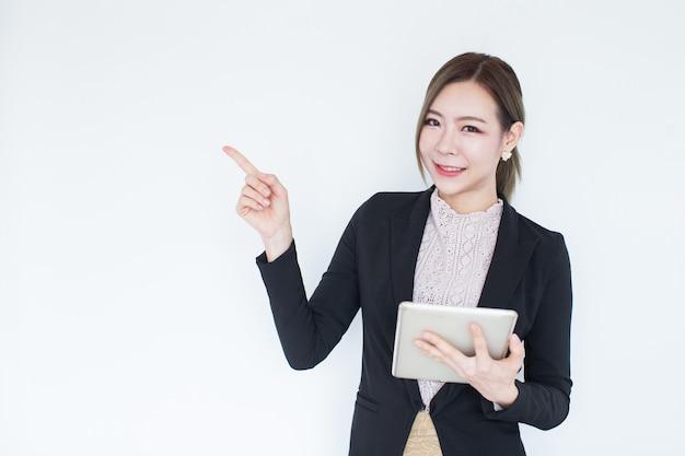 タブレット技術で笑顔の若いアジアビジネス女性 Premium写真
