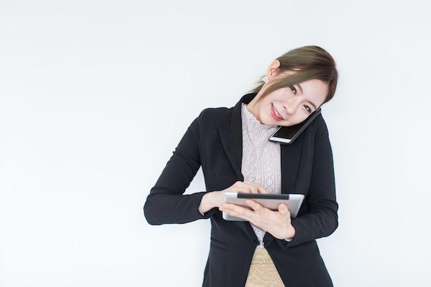 タブレット技術とスマートフォンを持つ若いアジアビジネス女性の笑みを浮かべてください。 Premium写真