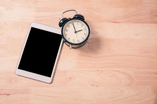 レトロな目覚まし時計とウッドバックグラウンドプロセスヴィンテージ色のデジタルタブレットのスマートフォン Premium写真