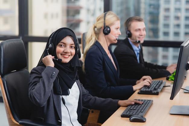 コールセンターでヘッドセットで話しているサービスデスクコンサルタント顧客サービススタッフ作業若い美しいアジアのイスラム教徒の女性 Premium写真