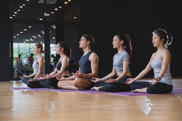 フィットネスクラブで健康的なライフスタイルのために一緒に瞑想ヨガを練習するミックスレースの人々のグループ Premium写真