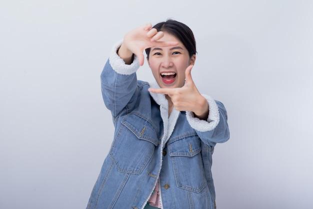 若いアジアの笑みを浮かべて興奮している女性の表情を驚かせ、驚いた、青いカジュアルな服の肖像画を着て幸せな白人少女 Premium写真