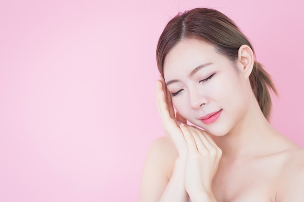 清潔でさわやかな肌に直面する美しい若い白人アジア女性笑顔は、自然な化粧品です。美容、スキンケア、洗顔 Premium写真