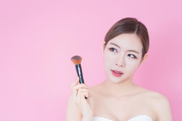 化粧品のブラシの粉を適用する若い美しい白人アジア女性の肖像画。美容、スキンケア、洗顔 Premium写真