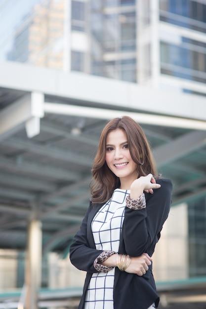 自信を持って、笑みを浮かべて探している成功したスマートビジネス女性の肖像画 Premium写真