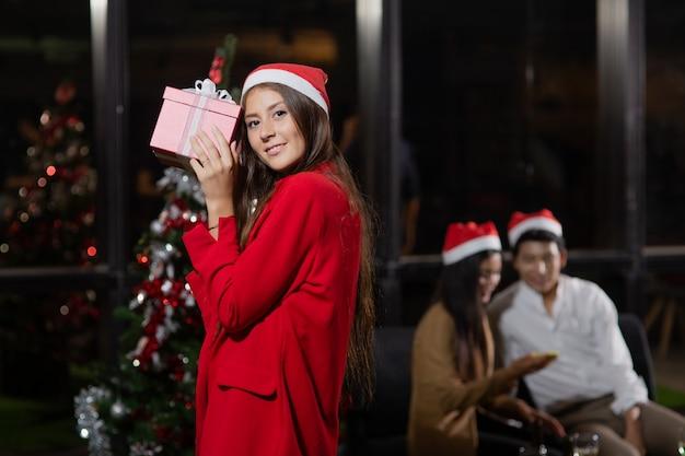 クリスマスパーティーのための彼女の同僚のギフトボックスの前面を保持している白人の美しい少女。 Premium写真