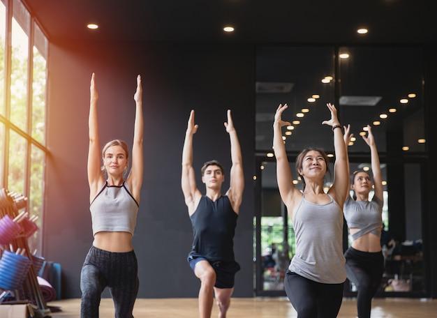 Группа людей смешанной расы, практикующих йогу вместе медитируя на здоровый образ жизни в фитнес-клубе Premium Фотографии