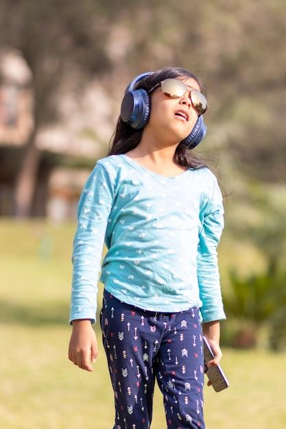 公園で彼女のヘッドフォンでスマートフォンで音楽を聴く少女 Premium写真