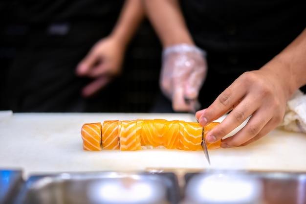 レストランで寿司を作る日本人シェフ。日本の伝統的な食べ物、サーモン巻き寿司。 Premium写真
