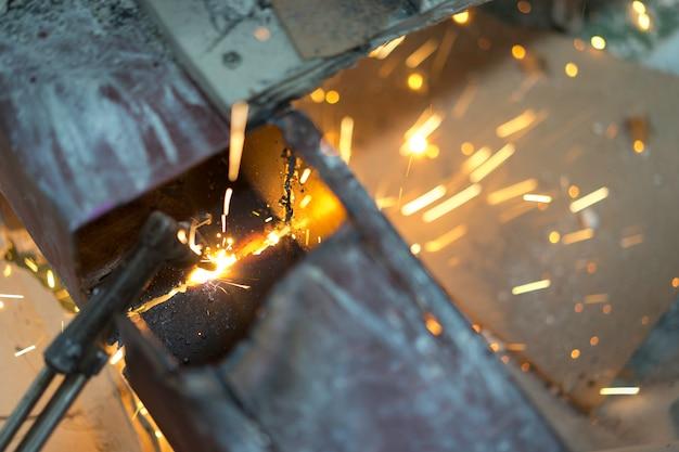 Работник делает искры от сварки стали на рабочем месте. Premium Фотографии