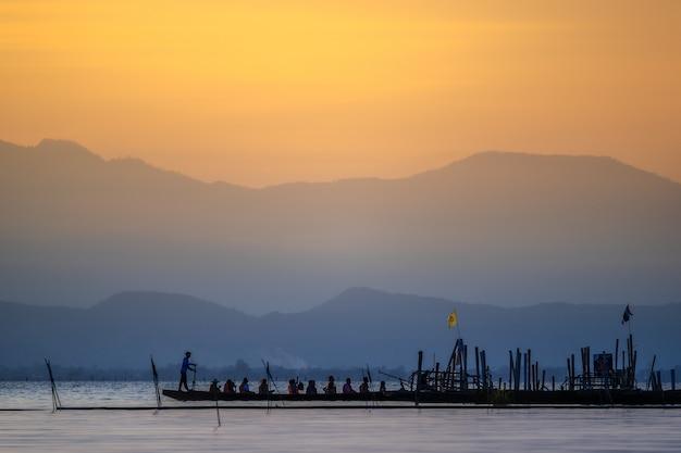 Силуэт азиатских туристов расслабляющий на деревянной лодке. Premium Фотографии