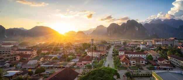 Красивый закат над горами и маленькая деревня с закатом сумеречного неба в четном Premium Фотографии