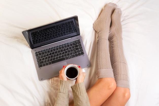 ノートパソコンと一杯のコーヒーを手に、ベッドの上の女性のソフト写真トップビューポイント Premium写真