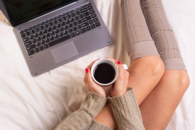 ノートパソコンと手、トップビューポイントでのコーヒーカップとベッドの上の女 Premium写真