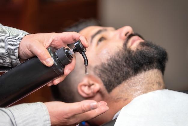 理髪店でローションを剃った後に適用するヘアスタイリスト。 Premium写真