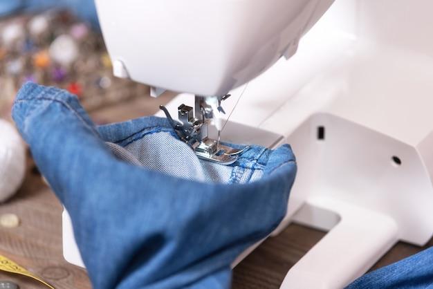 Швейные джинсовые джинсы со швейной машиной. ремонт джинсов на швейной машинке. Premium Фотографии