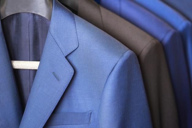 戸棚にぶら下がっている豪華なスタイルの紳士服行を閉じます。 Premium写真