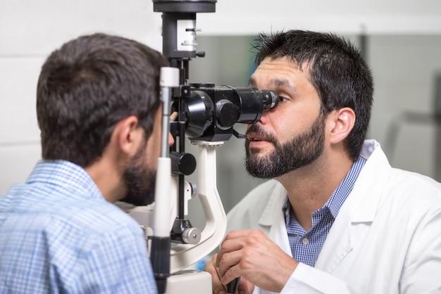 男性医師眼科医は近代的な診療所でハンサムな若い男の視力をチェックします。 Premium写真