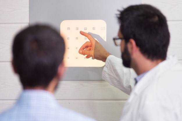 患者が視力検査表を読んでいる間に文字を指す眼科医。 Premium写真