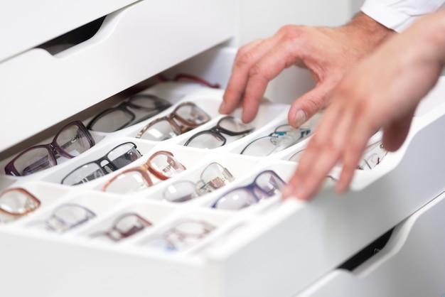 眼科医の手がクローズアップ、眼鏡店の引き出しからメガネを選択します。 Premium写真