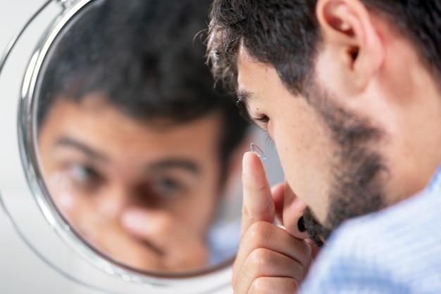 Человек надевая контактные линзы в клинике офтальмологии. Premium Фотографии