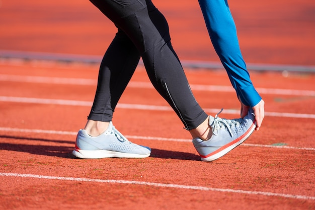 Крупным планом зрения, спортсмен растяжения на беговой дорожке. Premium Фотографии