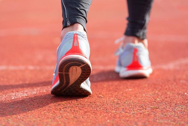 Крупным планом зрения спортсмена, готовится к гонке на беговой дорожке. сосредоточьтесь на ботинке атлета, готовящегося к гонке на стадионе Premium Фотографии