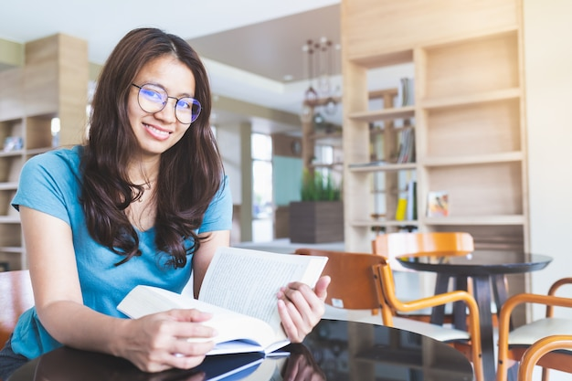 眼鏡をかけているアジアの女性は笑みを浮かべて、図書館で本を読んでいます。 Premium写真