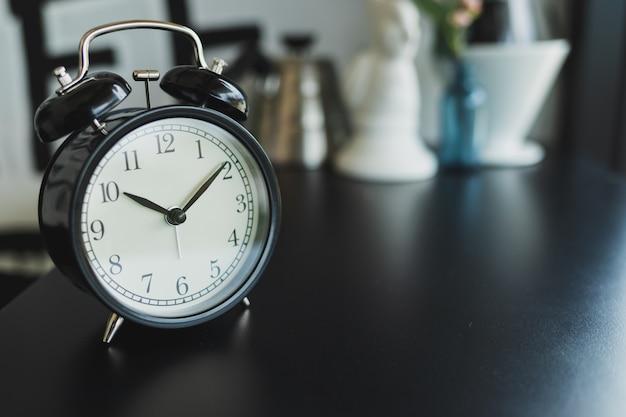 黒の木製テーブル、背景をぼかした写真に置かれたヴィンテージ黒目覚まし時計を閉じる Premium写真