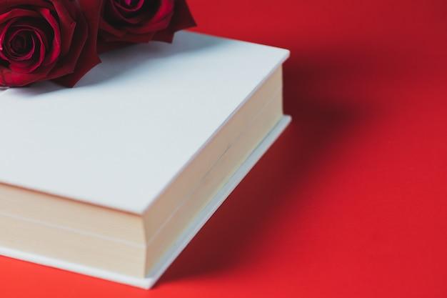赤いバラホワイトブックに配置赤いテーブル、コンセプト、バレンタインデーのテーマ Premium写真