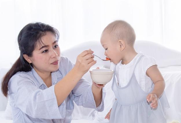 Мать кормит фрукты своей малышке в постели Premium Фотографии