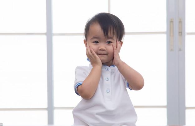 Любопытство азиатский малыш прекрасная девушка озорной веселый играть в одиночестве в домашнем офисе отца, улыбаясь очаровательны дочь, глядя в камеру с счастливым, сидя на столе с офис стационарный фон, счастливый ребенок Premium Фотографии