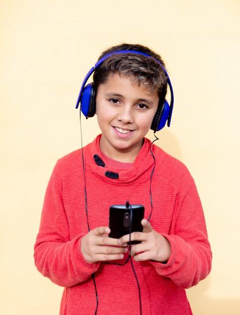 青いハドフォンと携帯電話で音楽を聴く黒髪の子 Premium写真