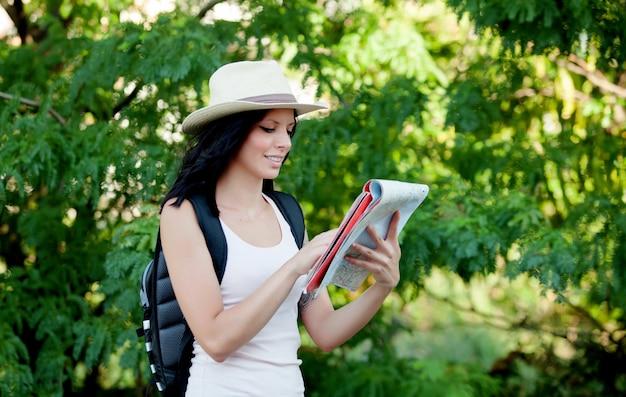 地図を参照しながら森を歩いているブルネットの女性 Premium写真