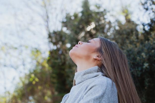 大きな石に座っている若い女性 Premium写真