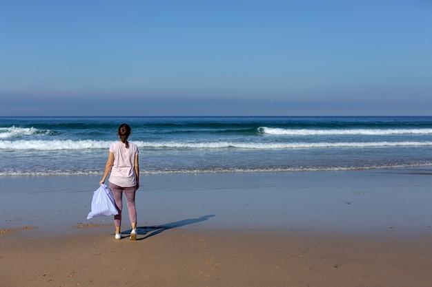 Женщина собирает мусор и пластмассы, чистит пляж Premium Фотографии