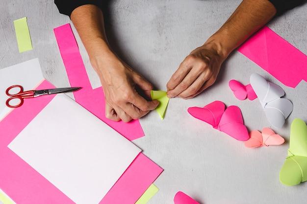 Руки женщины делают оригами из бумаги Premium Фотографии