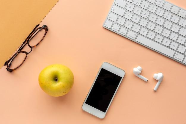 アップル、キーボード、イヤホン、スマートフォン、メガネを備えたワークスペース Premium写真