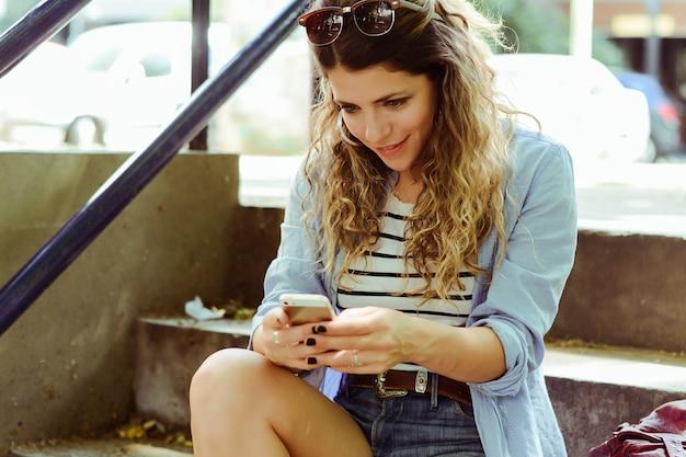 若い女性がスマートフォンでメッセージを送信します。 Premium写真