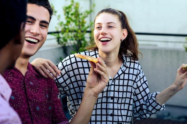 ピザと飲み物のボトルを持つ若い友人のグループ Premium写真